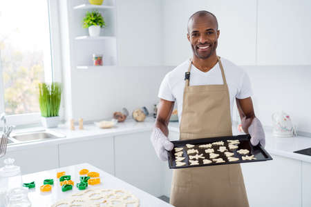 Portrait of his he nice attractive cheerful cheery guy baking handmade snack pie cake cookies studying learning teaching courses classes lesson in modern light white interior house kitchen