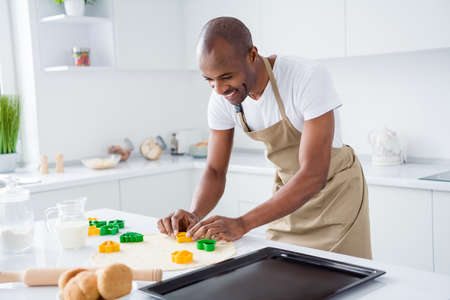 Portrait of nice attractive cheerful cheery focused guy making handmade pie cake using form shape holiday day easter having fun in modern light white interior house kitchen