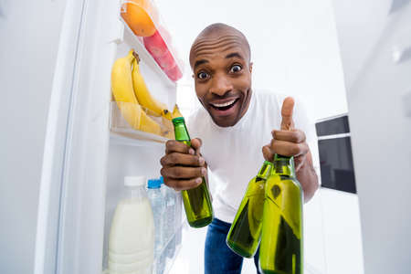 Portrait of his he nice attractive glad funky cheerful cheery guy looking in fridge taking limonade bottles preparing cool party in modern light white interior house kitchen indoors