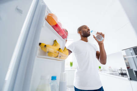 Portrait of his he nice attractive dreamy healthy guy taking in fridge fresh beverage mineral artesian source water daily everyday regime in light white interior house kitchen indoors