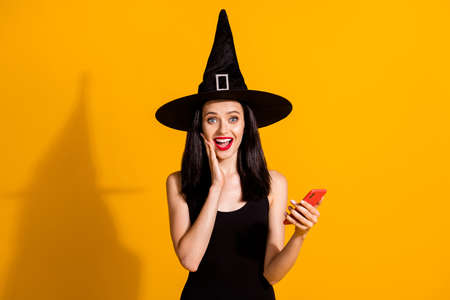 Photo of pretty lovely young magician lady hold telephone hand cheek open mouth excited find online shop discount wear black wizard headwear dress isolated bright yellow color background
