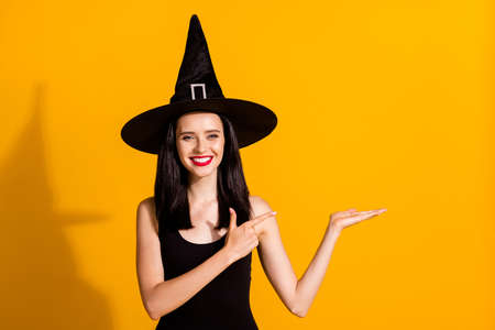Photo of cute pretty young magician lady toothy smile hold empty space directing finger make perfect recommendation wear black wizard headwear dress isolated bright yellow color background