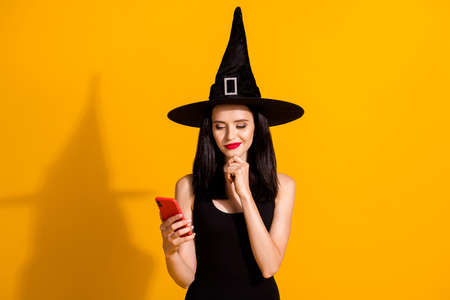 Fake or not. Photo of cute charming young magician lady hand chin hold telephone thinking read online news wear black wizard headwear dress isolated bright yellow color background