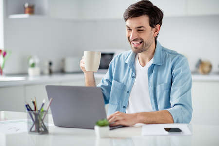 Photo of handsome guy young student browsing notebook sitting table video call teacher work house online lesson conference friendly talk drink tea good mood social distance quarantine indoors