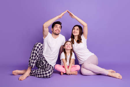 Portrait of nice cheerful full family dad mom offspring daughter wearing pajama sitting on floor showing roof flat house isolated on bright vivid shine vibrant violet color background Standard-Bild