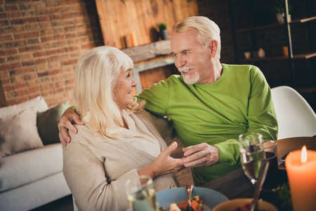 Portrait of his he her she nice adorable attractive lovely cheerful couple embracing eating luncheon meal domestic restaurant leisure talk speak at modern loft industrial brick interior house