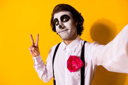 Self-portrait of nice handsome creepy scary baleful cheery malicious guy catrina celebratory having fun showing v-sign social influencer isolated bright vivid shine vibrant yellow color background