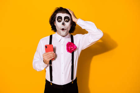 Portrait of his he nice handsome spooky wondered stunned astonished amazed guy using device fake news calavera blog post comment reaction isolated bright vivid shine vibrant yellow color background