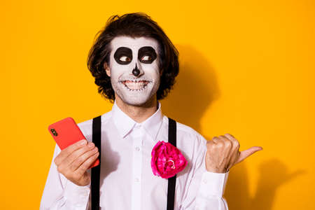 Close-up portrait of his he nice handsome spooky cheerful glad guy using device app 5g smm showing copy space advice calavera look idea isolated bright vivid shine vibrant yellow color background Stock Photo