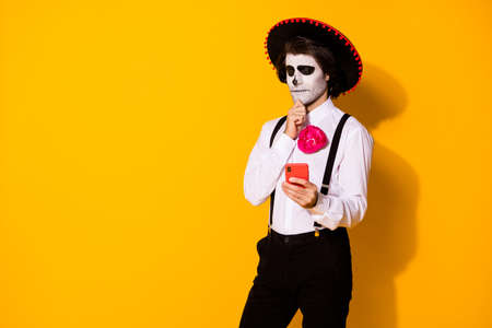 Portrait of his he nice handsome spooky minded pensive guy caballero using device app 5g thinking creating blog calavera celebration isolated bright vivid shine vibrant yellow color background