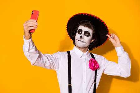 Close-up portrait of his he nice handsome painted creepy cheery guy caballero taking making selfie calavera celebratory look outfit isolated bright vivid shine vibrant yellow color background