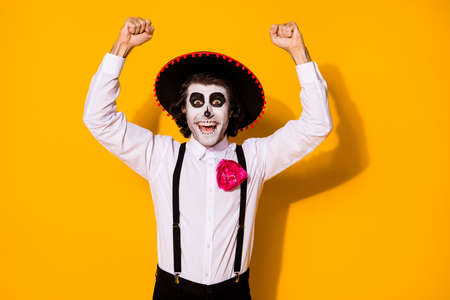 Photo of spooky monster guy raise hand fists winning huge prize festival theme event competition wear white shirt death costume sugar skull suspenders isolated yellow color background
