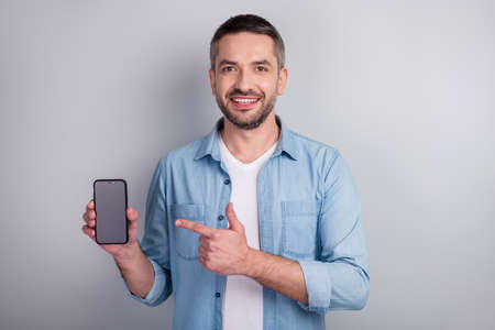 Close-up portrait of his he nice attractive content cheerful cheery guy demonstrating new cool digital device ad advert modern technology isolated over gray light pastel color background Archivio Fotografico