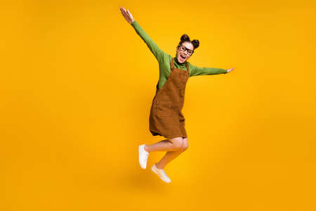Full length photo of cheerful dreamy girl nerd high school student jump hold hand fly like bird wear green sweater skirt overall gumshoes isolated over bright shine color background