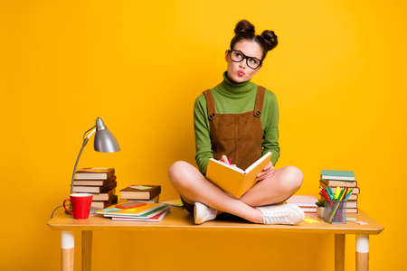 Full length photo of minded pensive girl sit table legs crossed write copybook look copyspace think thoughts wear green pullover dress skirt overall isolated bright shine color background