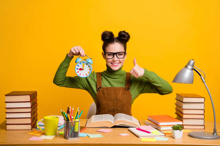 Photo of positive girl high school student sit table prepare exam hold clock show thumb up sign wear green sweater isolated over bright shine color background