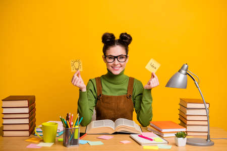 Photo of pretty librarian lady worker fond of reading love her job hold two paper cards creative smart clever person sitting table wear pullover specs overall isolated vivid color background