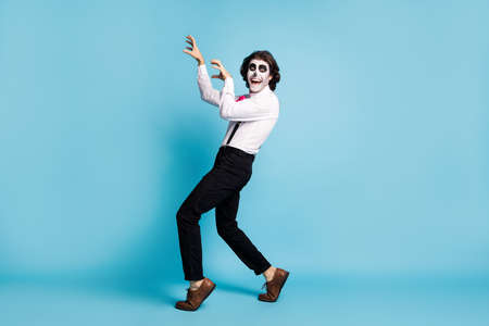 Full length body size view of handsome funky cheerful cheery scary creepy baleful malicious gentleman having fun zombie scratching attack isolated bright vivid shine vibrant blue color background