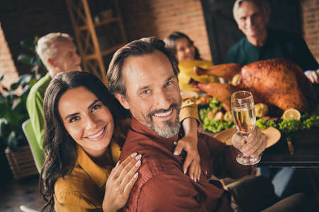 Congratulations. Photo of full family gathering bristled father wife embrace shiny smiling hold wineglass drink champagne served dinner big table generation in evening living room indoors Standard-Bild