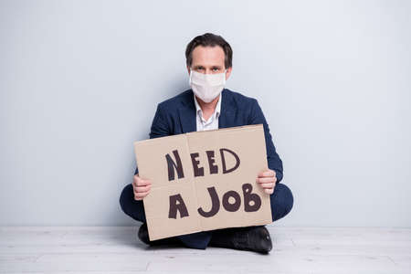 Portrait of serious fired clerk guy agent broker realtor wearing safety mask holding in hands carton cardboard poster saying need a job global economy infection isolated grey pastel color background