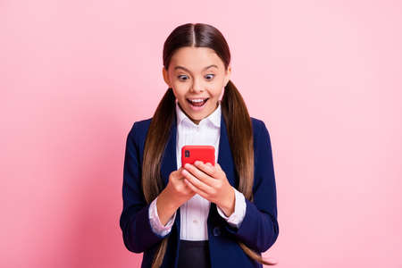 Portrait of her she nice attractive cheerful addicted glad small little girl holding in hands gadget using app 5g smm like follow subscribe isolated over pink pastel color background Stock fotó