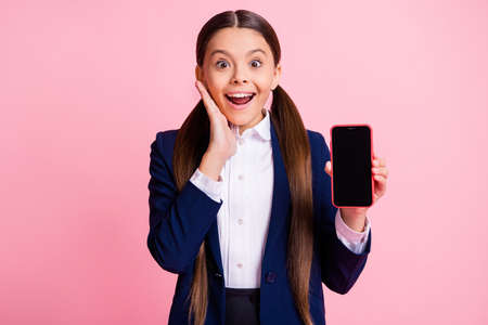 Portrait of her she nice attractive cheerful glad small little girl holding in hand gadget enjoying web service app 5g roaming cellular fast speed isolated over pink pastel color background
