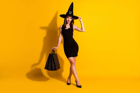 Full length body size view of her she nice attractive pretty thin cheerful chic lady wizard carrying new things clothes touching cone hat isolated bright vivid shine vibrant yellow color background Imagens