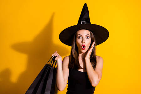 Close-up portrait of her she attractive pretty amazed wondered stunned brown-haired lady wizard carrying new clothes season bargain pout lip isolated bright vivid shine vibrant yellow color background Stock fotó