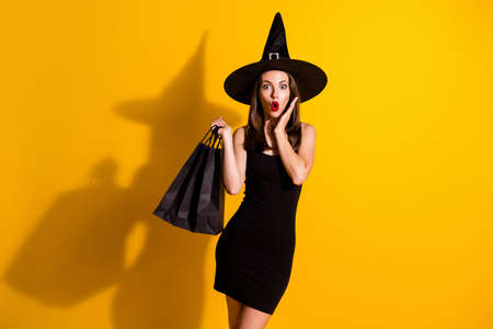 Portrait of her she nice attractive pretty amazed wondered stunned cheery thin lady wizard carrying new clothes season bargain news isolated bright vivid shine vibrant yellow color background