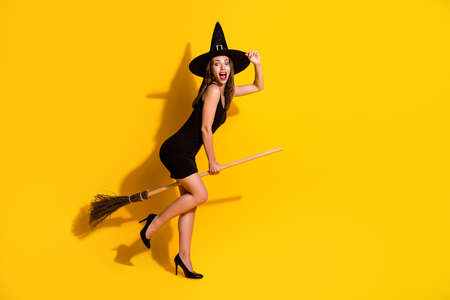 Full length body size profile side view of her she attractive ecstatic cheerful cheery lady wizard riding broom having fun event magic isolated bright vivid shine vibrant yellow color background Stock fotó