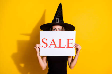 Portrait of her she nice attractive pretty funny amazed lady wearing cone hat holding in hands paper promo card sale hiding face isolated over bright vivid shine vibrant yellow color background