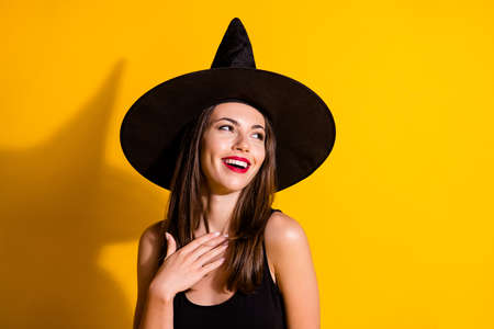 Photo of charming cute young lady smiling red bright lipstick coquettish look up empty space hand chest fall event wear black witch costume cone headwear isolated yellow color background