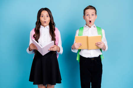 Photo of two small girl boy schoolkids classmates hold copybook open mouth shock read incredible history facts wear bag white shirt black pants dress isolated blue color background Stock fotó