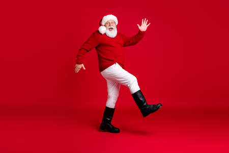Full body profile side photo funny old man retired pensioner santa claus headwear go walk copyspace jolly holly tradition event wear x-mas outfit boots isolated bright shine color background