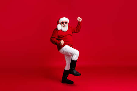 Full size photo of crazy old man in santa claus headwear raise fists win shopping season fairy x-mas sale wear pants trousers boots isolated over bright shine color background