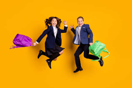 Full length body size view of two nice attractive small little cheerful friends friendship jumping having fun new academic year isolated bright vivid shine vibrant yellow color background