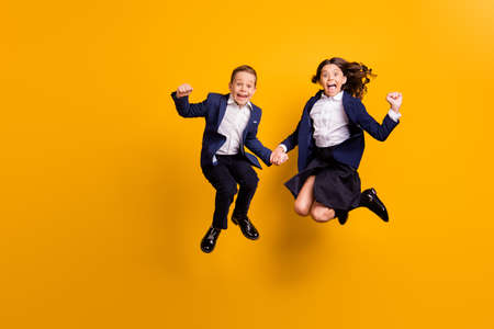 Full length body size view of attractive small little crazy cheerful cheery ecstatic schoolkids jumping having fun great news reaction isolated over bright vivid shine vibrant yellow color background