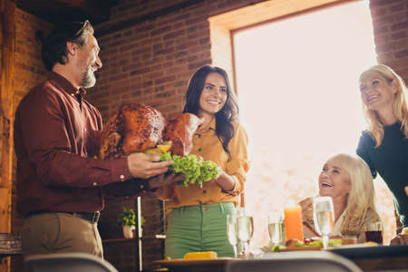 Young couple carry large decorated turkey just from grill living room holiday dinner chicken family recipe indoors
