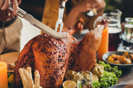 Close up photo of served table thanks giving dinner knife cut down stuffed grilled turkey living room indoors
