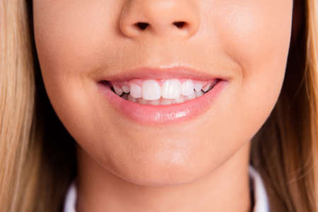 Close up cropped photo of charming lovely schoolgirl little lady mouth pink balm shiny toothy white smile teeth hygiene dentist clinic promo healthy oral care disease prevention concept Stock Photo