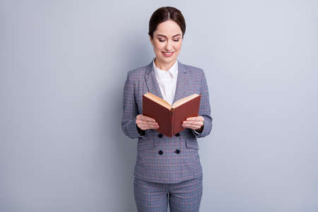 Portrait of her she nice attractive focused knowledgeable intellectual skilled cheerful teacher wearing casual checkered suit reading academic dictionary isolated grey pastel color background Stock Photo