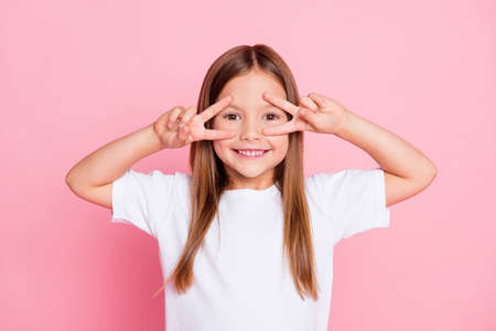 Photo of nice adorable pretty kid enjoy spring free time make v-sign wear good look clothes isolated over pink color background Foto de archivo