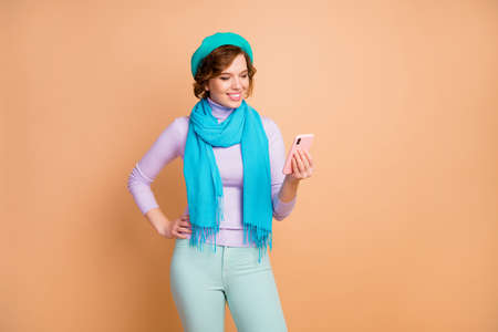 Portrait of her she nice attractive lovely pretty charming cheerful cheery girl using cell browsing internet online 5g media smm isolated over beige pastel color background