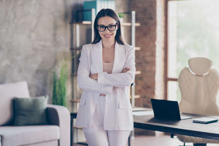 Portrait of her she nice-looking attractive pretty cheerful lady qualified shark investor real estate agency owner folded arms at modern industrial loft brick interior workplace workstation Stock fotó