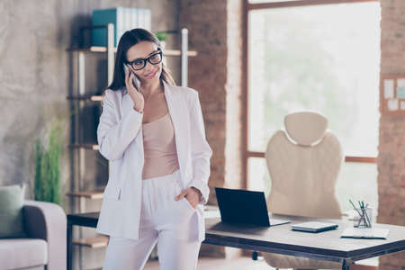 Photo of attractive beautiful business lady self-confident person talking partners communicating telephone home spacious office social distancing formal wear blazer pants white suit indoors Stock fotó