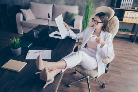 Photo of attractive business lady legs high-heels on desktop table remote work resting drink hot coffee break read paperwork contract home office social distance formal wear indoors Stock fotó