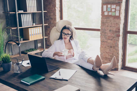 Photo of attractive business lady look screen notebook legs high-heels on desktop remote work staff study trainer coach resting drink hot coffee break home office social distance indoors