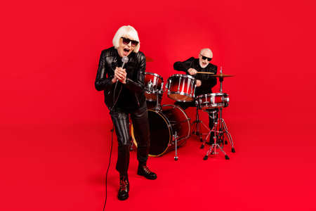 Full length photo of grey white hair two people pensioner wife husband rock band man play drum woman sing solo composition mic enjoy studio sound event isolated bright color background