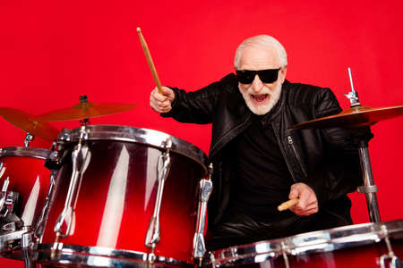 Portrait of crazy funky old man punk rocker play drum enjoy night club festival recording studio composition wear leather jacket isolated over bright shine color background Stockfoto