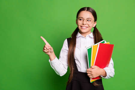 Photo of cute pretty small schoolkid lady in front of blackboard hold copybook direct finger interested cunning look empty space wear white shirt glasses isolated green color background